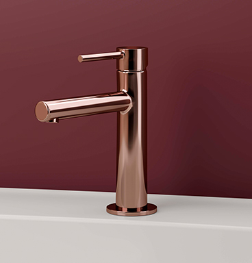 Close up of VitrA Origin copper basin mixer against dark red background